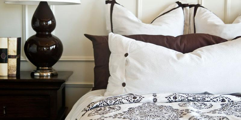 well-made bed with pillows and nightstand
